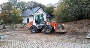 Трактор ровняет участок